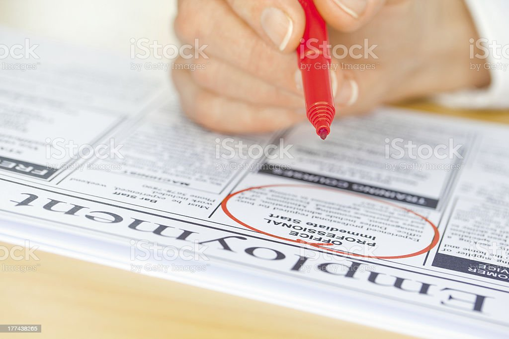 Hand with Red Pen Marking Job in Newspaper royalty-free stock photo