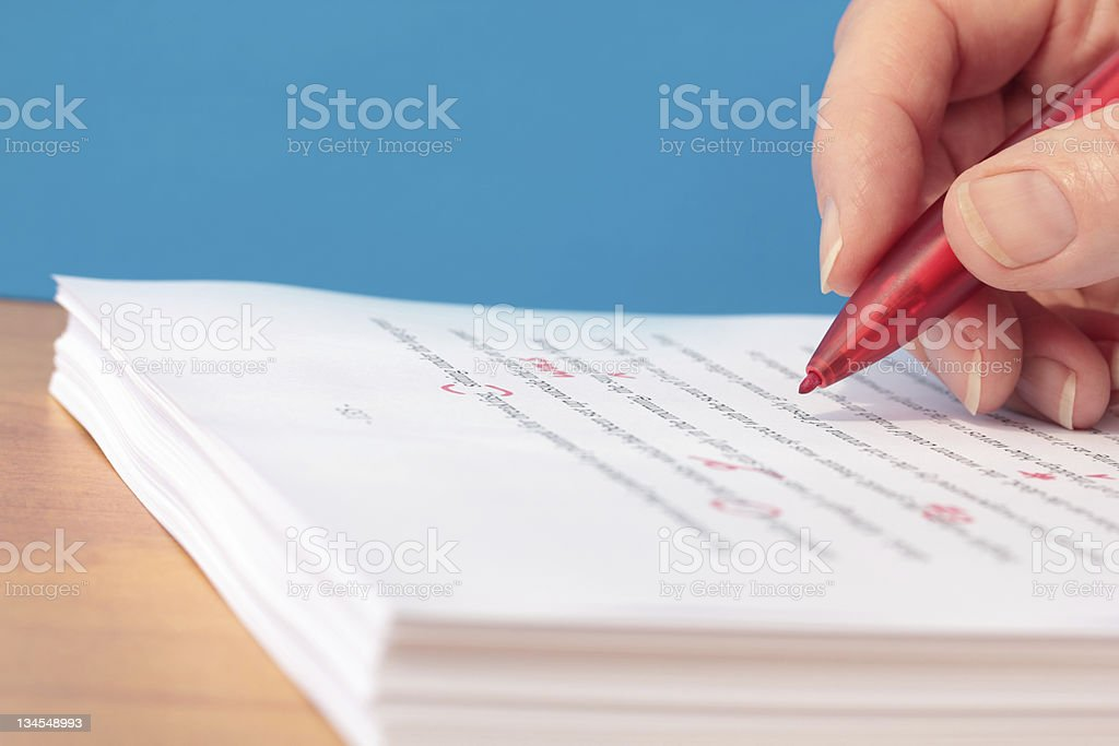 Hand with Red Pen Proofreading a Manuscript stock photo
