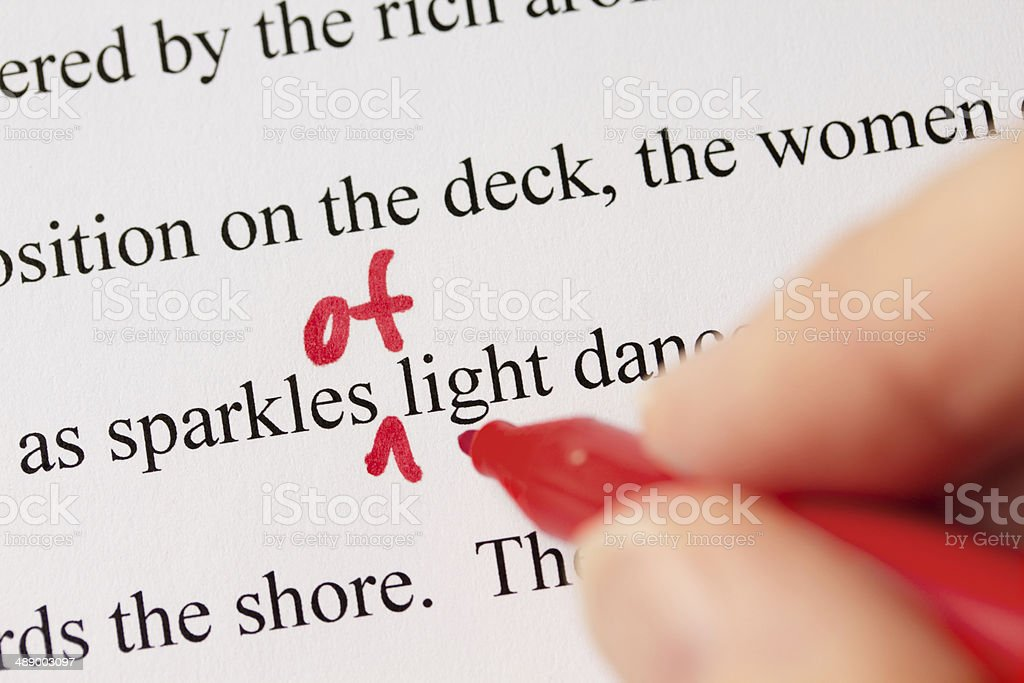 Hand with Red Pen Proofreading Text Closeup stock photo