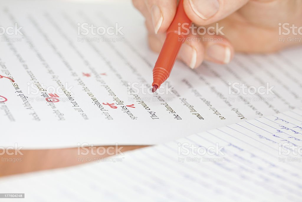 Hand with Red Pen Transcribing a Story stock photo