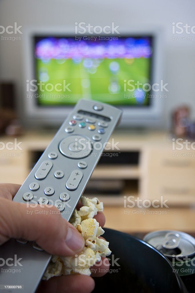 Hand with remote control and popcorn. royalty-free stock photo