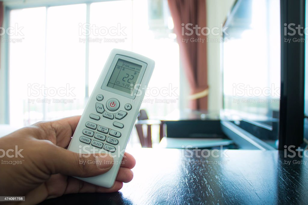 Hand with remote control directed on the conditioner stock photo