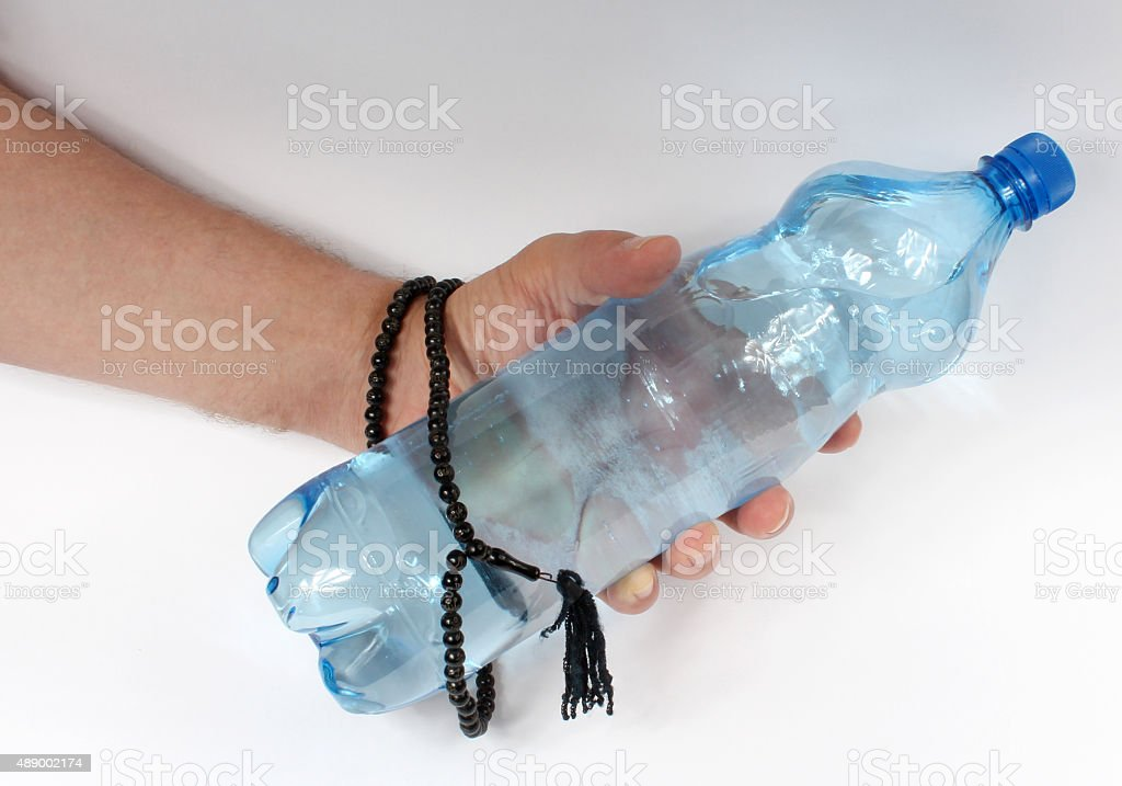 Hand with rosary and water stock photo