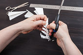 hand with scissors cut snowflake from paper