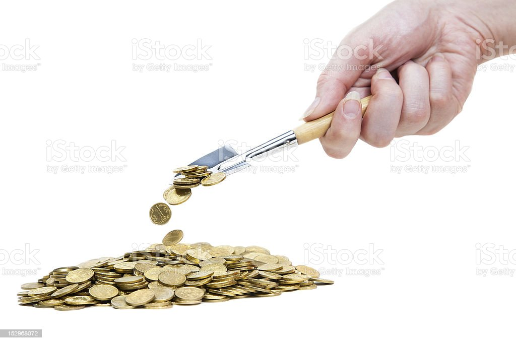 Hand with Shovel strewing coins on pile stock photo