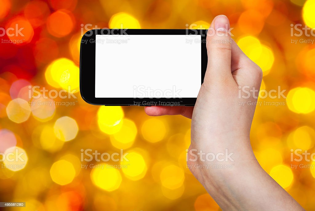 hand with smartphone on christmas background stock photo