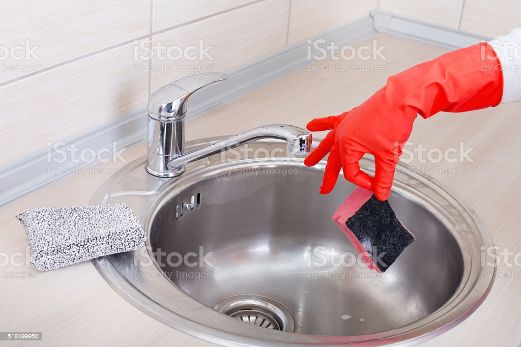 Hand with sponge above kitchen sink stock photo