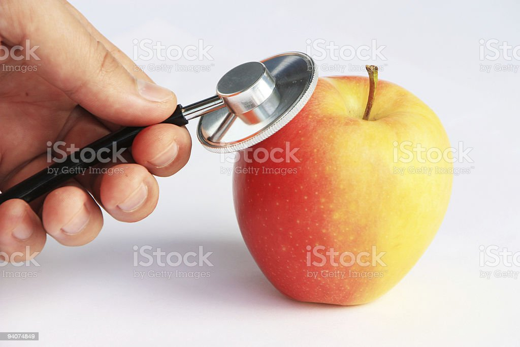hand with stethoscope consulting apple stock photo