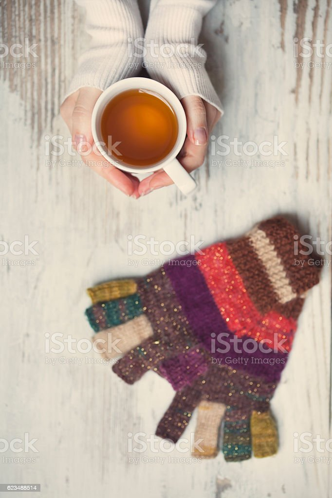 Hand with tea cup and fingerless gloves stock photo
