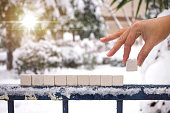 Hand with ten Blank Alphabet Stone Blocks on Metal Fence
