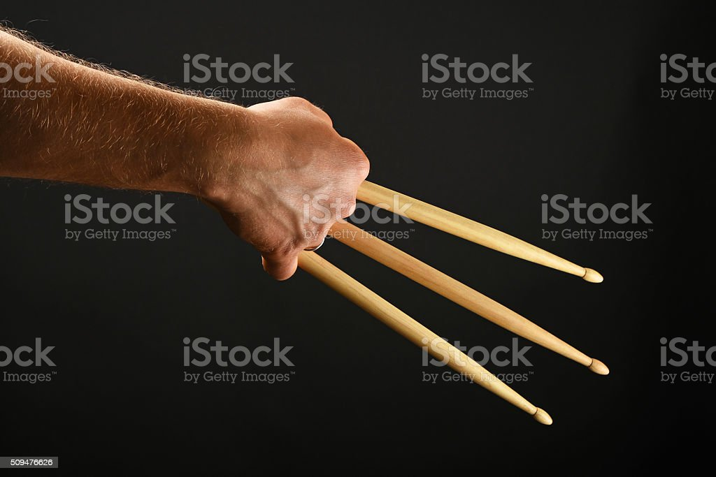 Hand with three drumsticks over black royalty-free stock photo