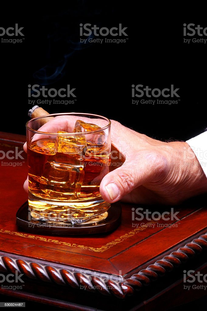 Hand with Whiskey Glass and Cigar stock photo