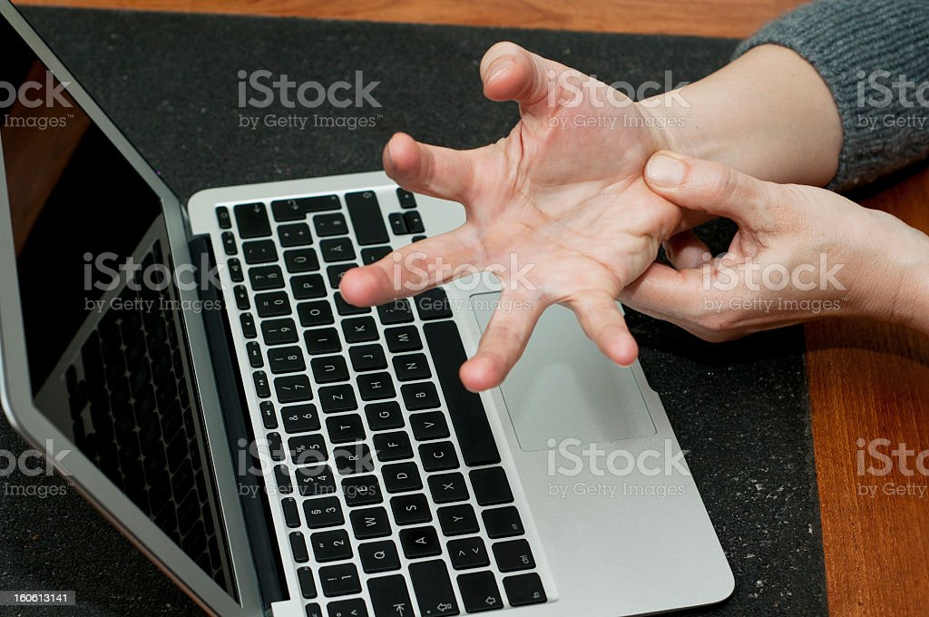 Hand with wrist pain and laptop on the background stock photo