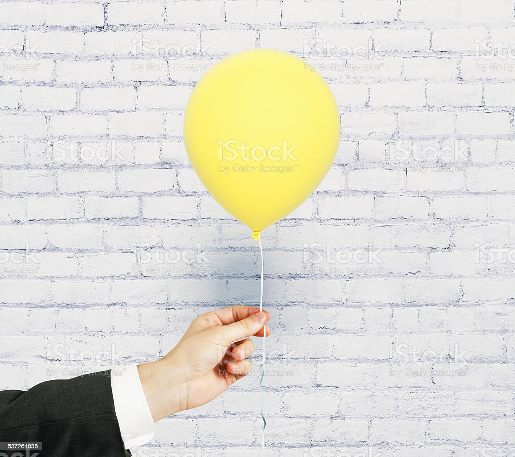 Hand with yellow balloon stock photo
