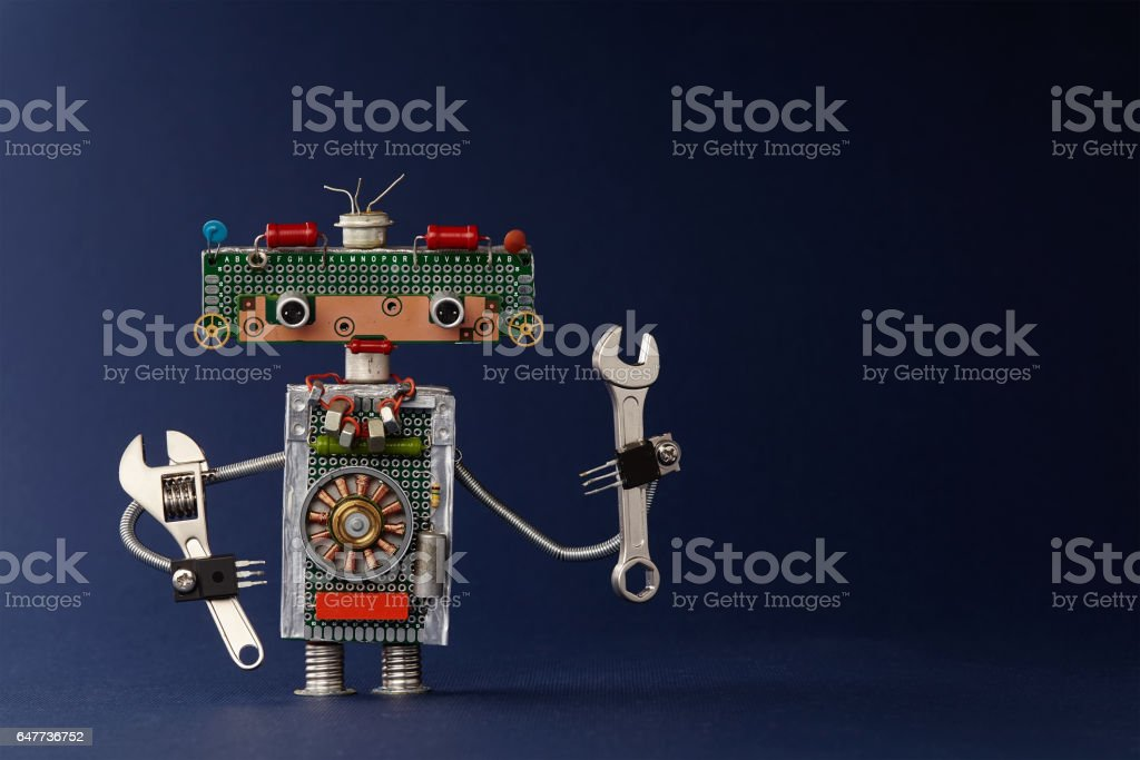 Hand wrench adjustable spanner robot handyman on dark blue paper background. Cute robotic toy made of electronic circuits, chip capacitors vintage resistors stock photo
