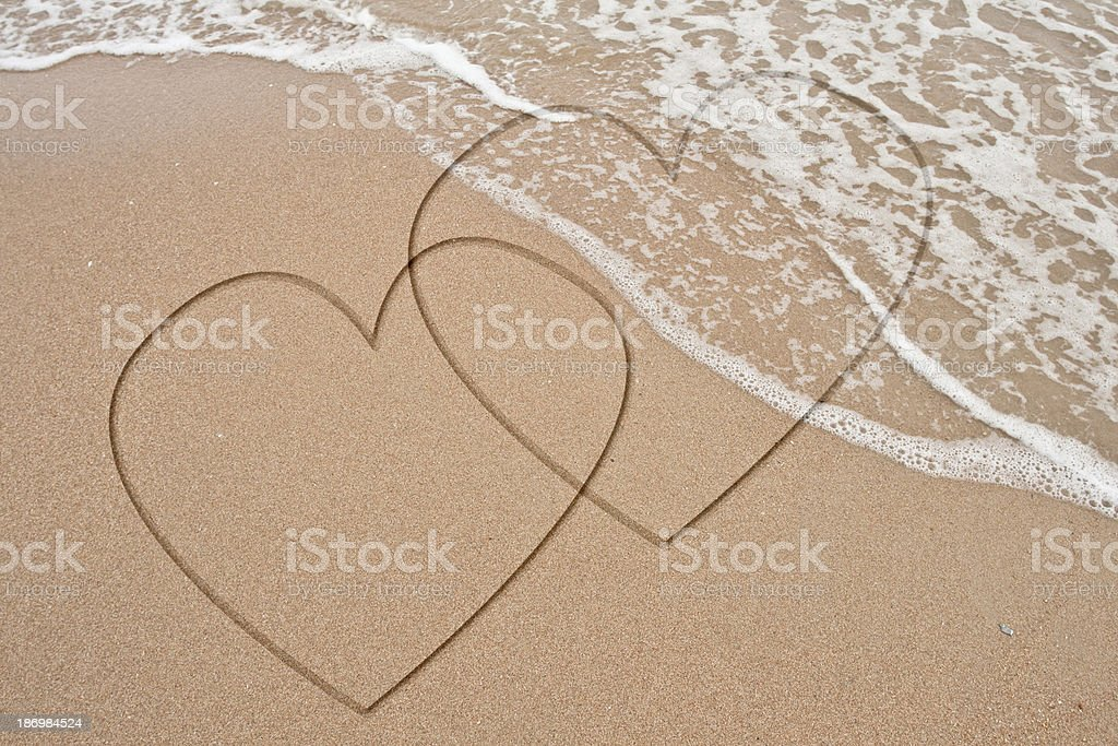 Hand write heart on sand erase by wave royalty-free stock photo