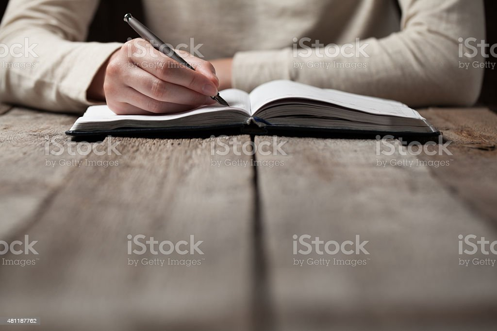 hand writes with a pen in a notebook stock photo