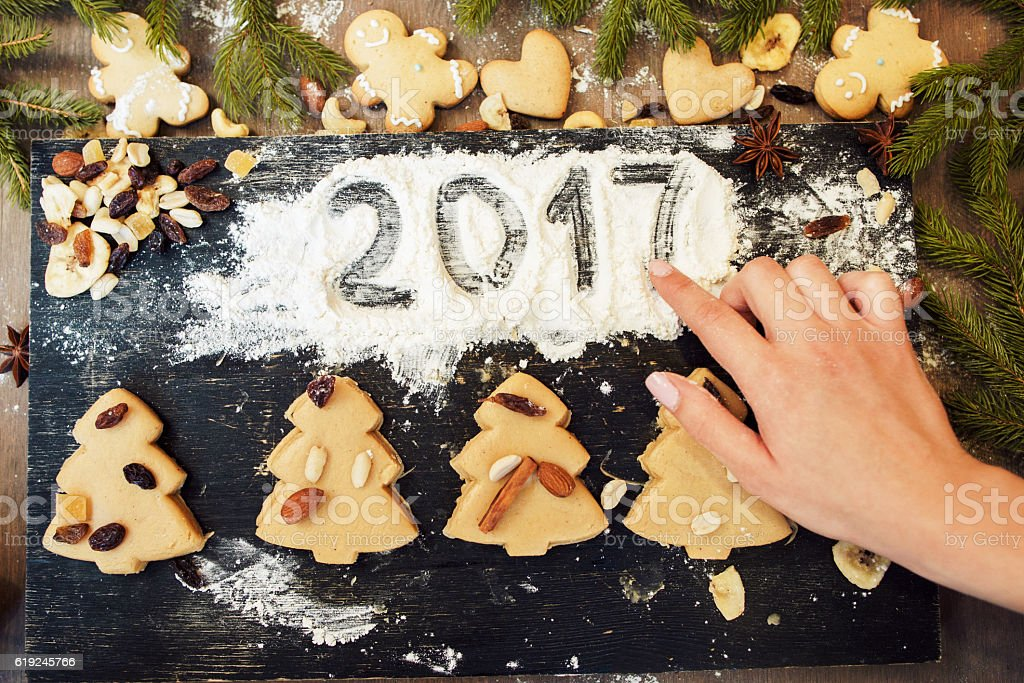 Hand writing 2017 on flour with gingerbread sweet stock photo