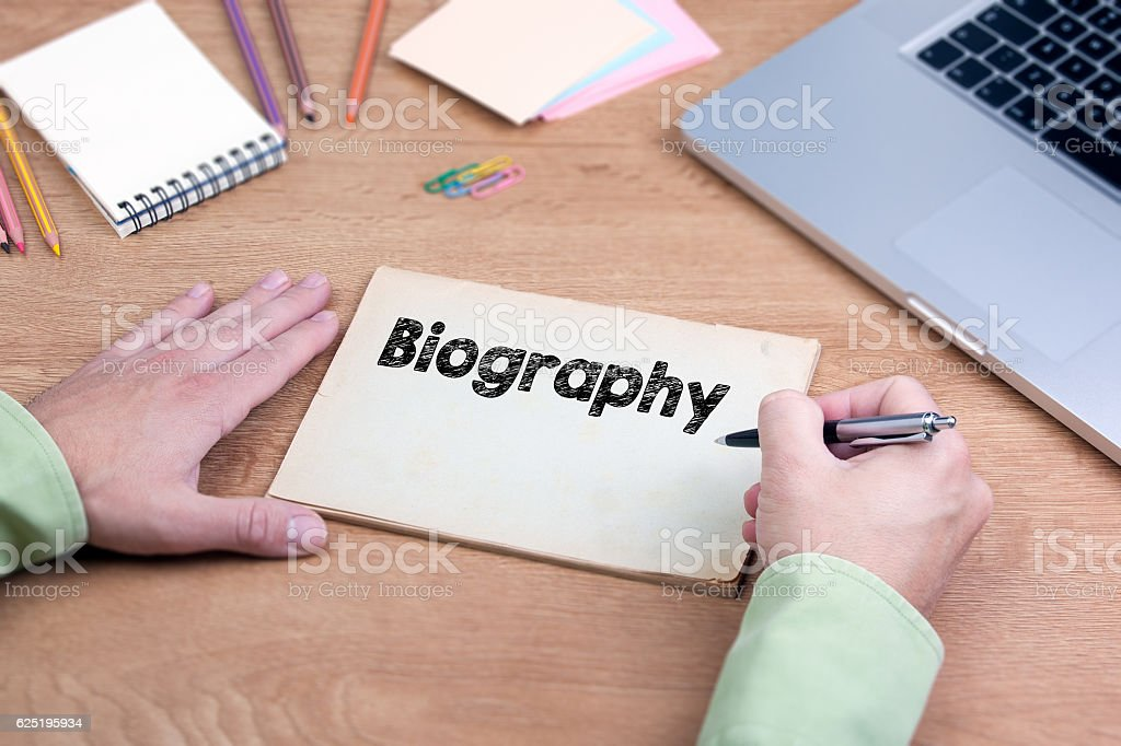 Hand writing Biography. Office desk with a laptop stock photo