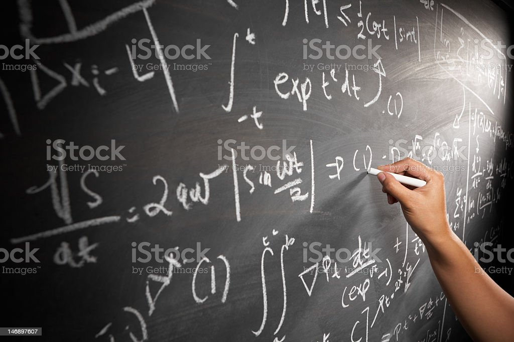 Hand writing equations with chalk on black board stock photo
