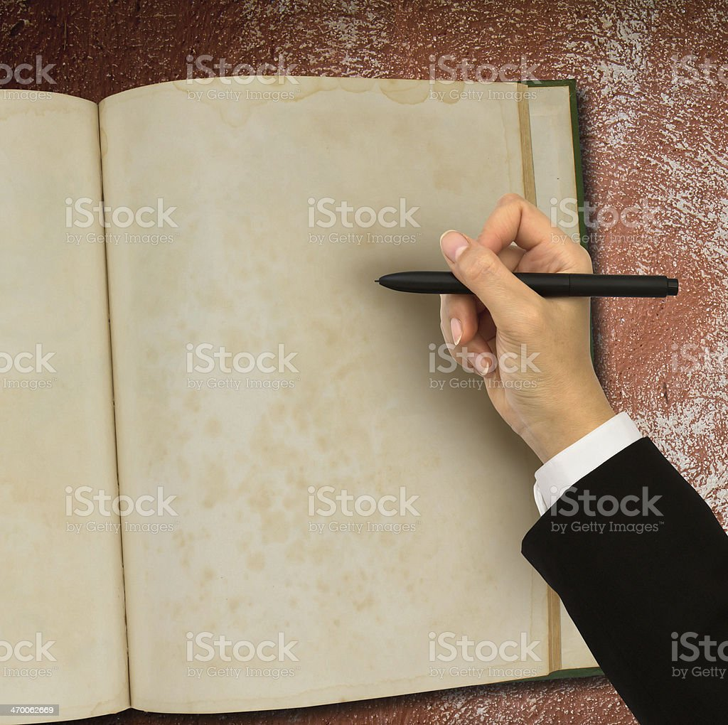 Hand writing in open old notebook on table royalty-free stock photo