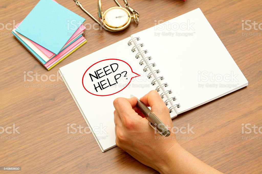 Hand writing NEED HELP? question on a notebook with pen. stock photo