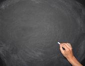 Hand writing on a blank empty blackboard