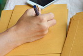 hand writing outside address on brown envelope