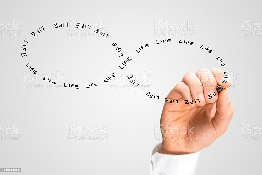 Hand Writing the Word Life in Figure Eight Shape stock photo