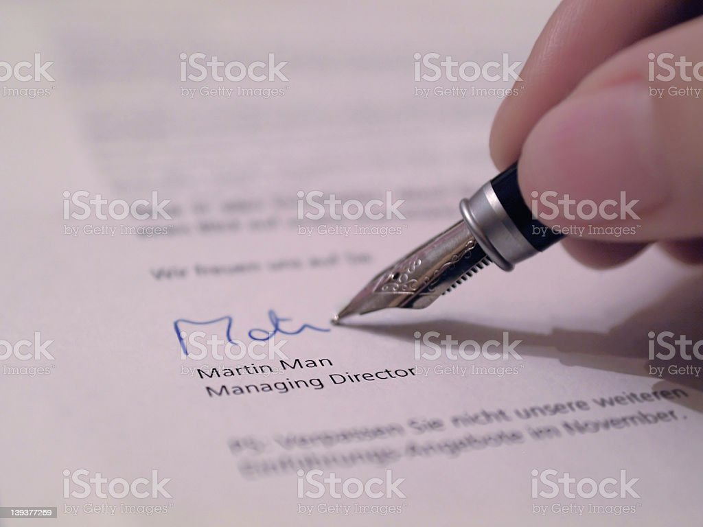 Hand writing their signature on a legal document stock photo