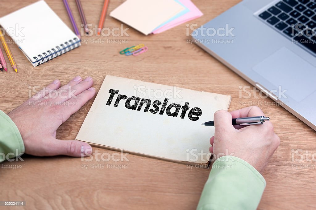 Hand writing Translate. Office desk with a laptop and stationery stock photo