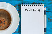 Hand writing We're Hiring on white paper with cup