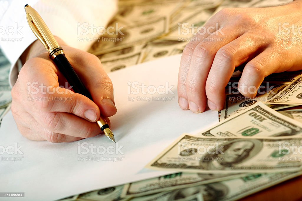 Hand writing with a gilded ink pen with dollars around. stock photo