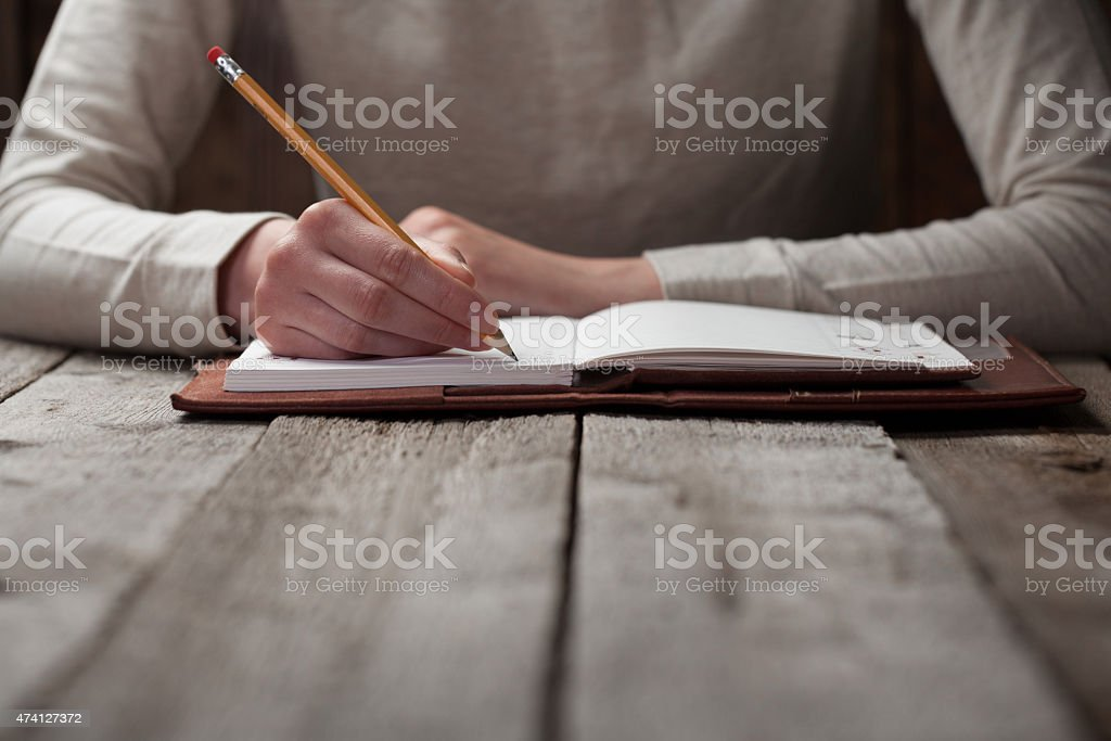 Hand writing with a pen in a notebook stock photo