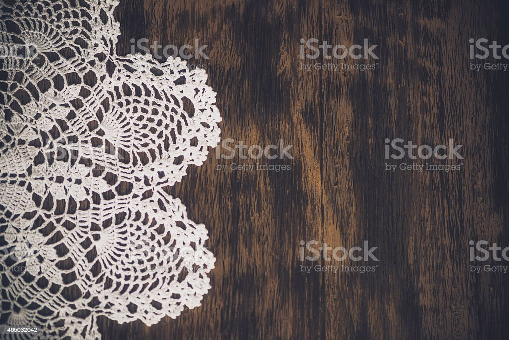 Handcrafted vintage lace doily against a contrasting wood plank. Backgrounds. stock photo
