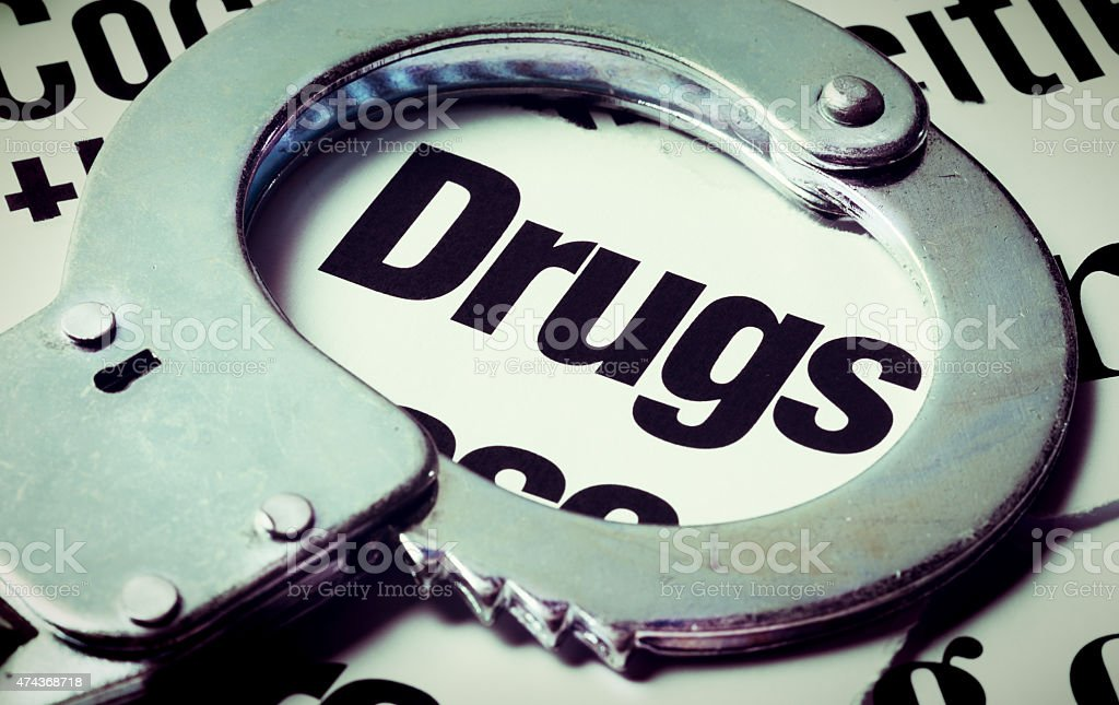 Handcuff frames the word 'drugs' in newspaper headlines stock photo