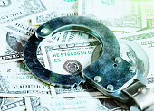 Handcuff on stack of US dollars: money and crime