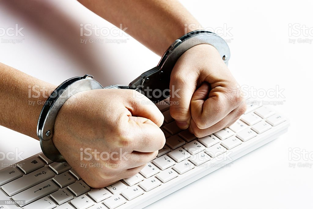 Handcuffed fists hit computer keyboard in frustration royalty-free stock photo