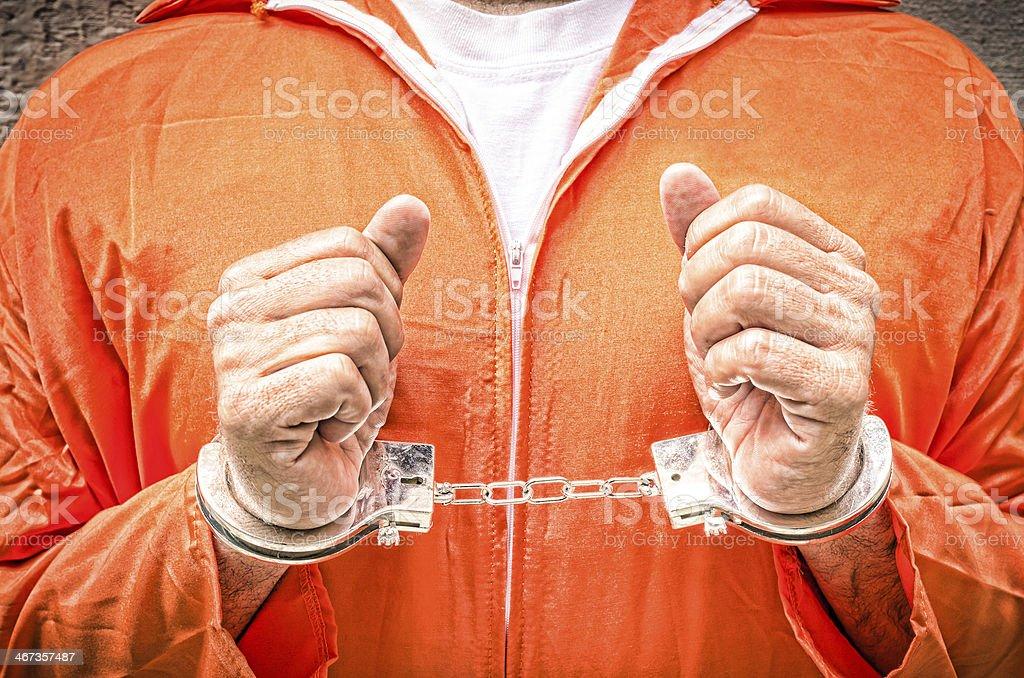 Handcuffed Hands - Guantanamo prison orange clothes stock photo