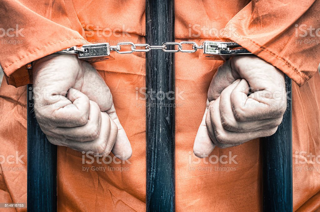 Handcuffed hands of a prisoner behind prison bars stock photo