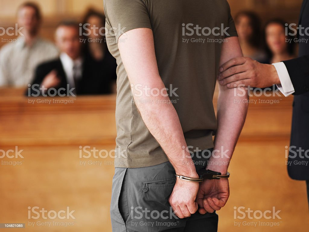 Handcuffed man standing in courtroom royalty-free stock photo