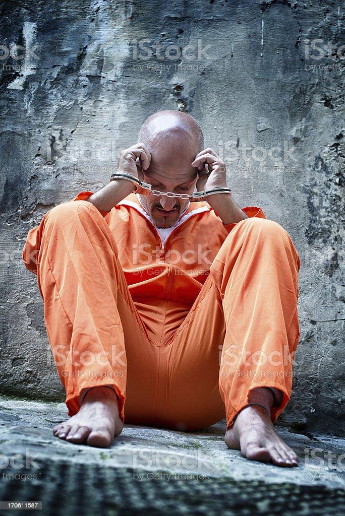 Handcuffed Prisoner in Orange Coveralls stock photo