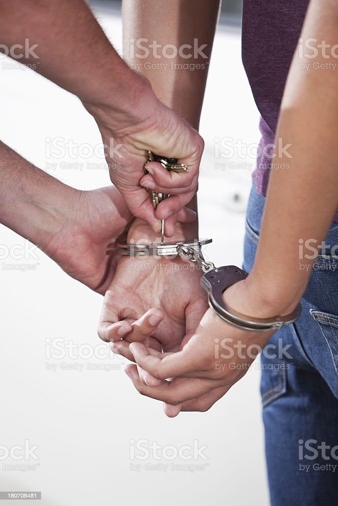 Handcuffed teenager being released stock photo