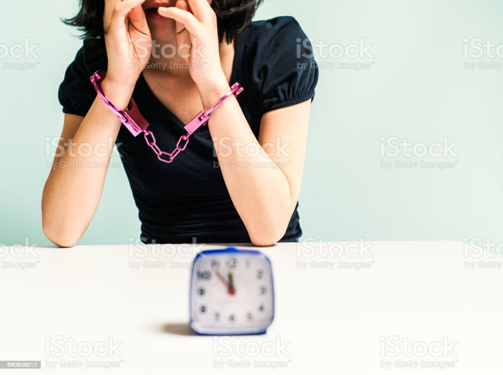Handcuffed woman and the time stock photo