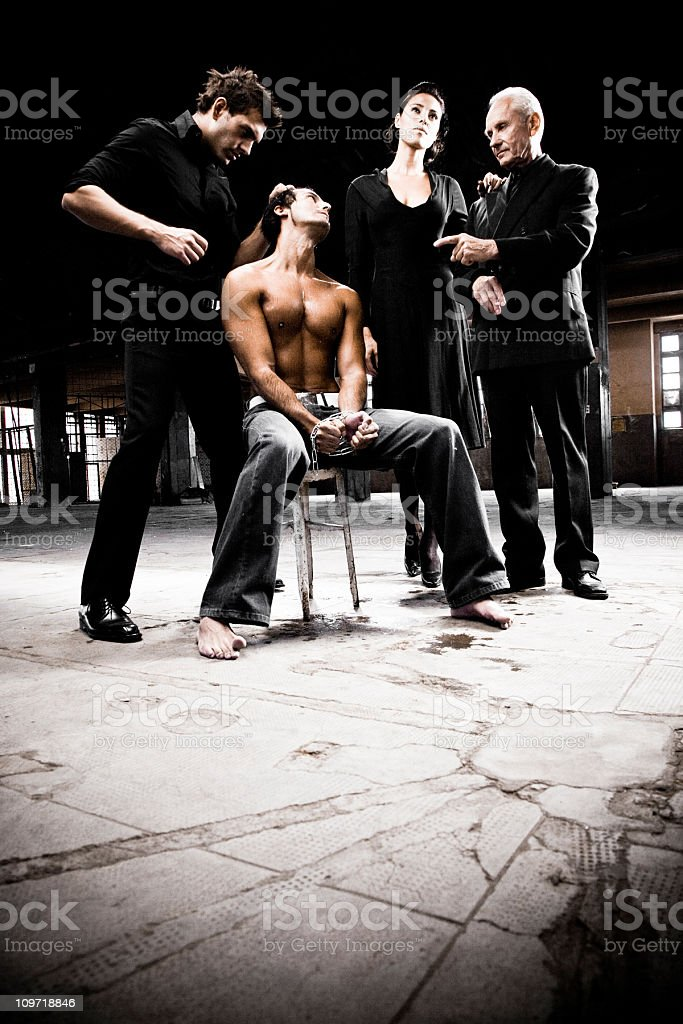 Handcuffed Young Man Surrounded by Three Mafia People royalty-free stock photo