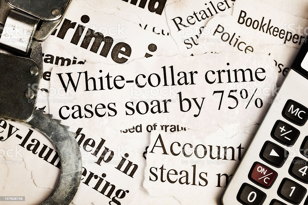 Handcuffs and calculator on headlines about white collar crime stock photo