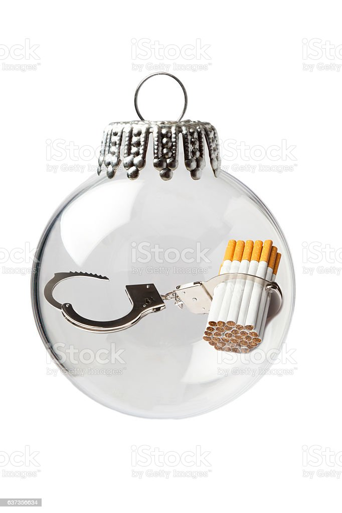 Handcuffs and Cigarettes in a Christmas Ornament stock photo