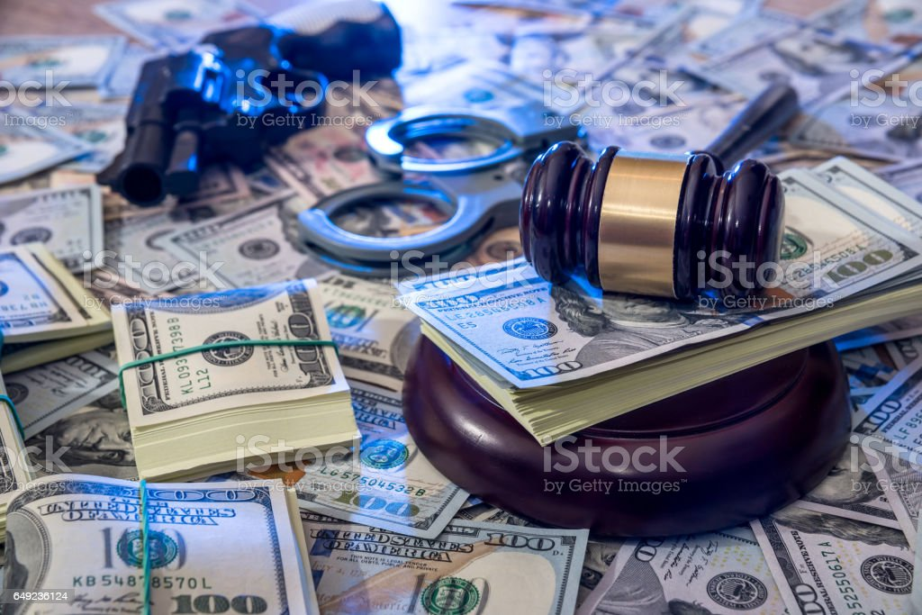 handcuffs and judge gavel, gun and money on brown wooden table. stock photo