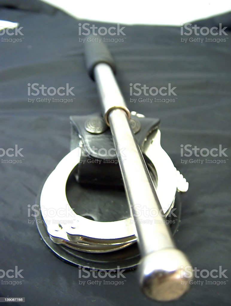 Handcuffs and telescope baton royalty-free stock photo