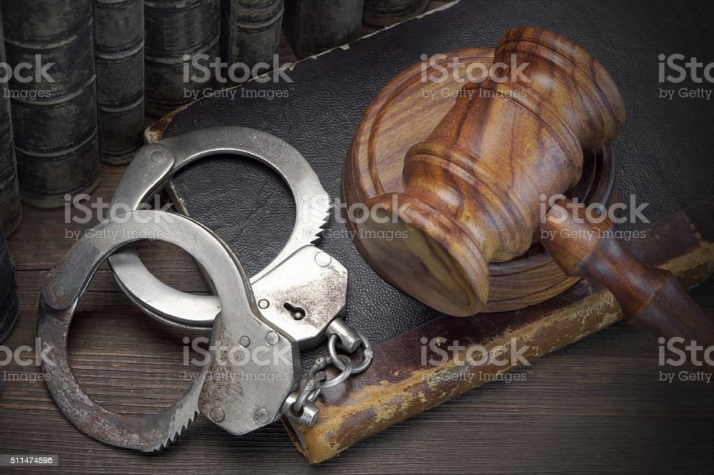 Handcuffs, Judge Gavel And Old Law Books On Wooden Table stock photo
